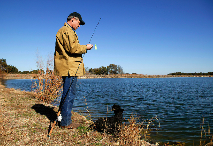 U.S. President George W. Bush goes fishing with his dog Barney on lake on the Bush Ranch in Crawford, Texas, December 29, 2003..Photo by Brooks Kraft/Corbis