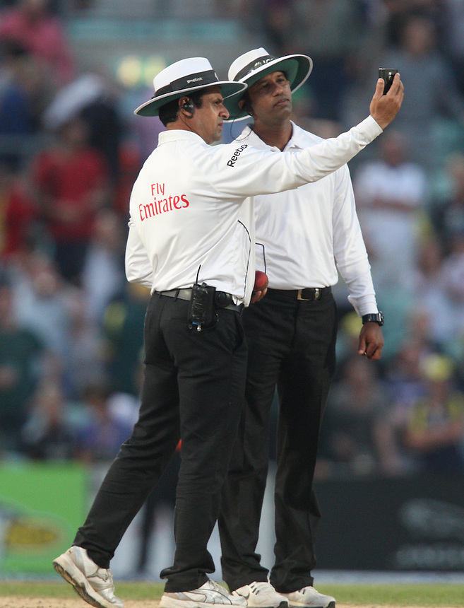 Umpires Aleem Dar (R) and Kumar Dharmasena take a light reading during day five<br /> <br /> Photo by Kieran Galvin / CameraSport<br /> <br /> International Cricket - Fifth Investec Ashes Test Match - England v Australia - Day 5 - Thursday 25th August 2013 - The Kia Oval - London<br /> <br /> &copy; CameraSport - 43 Linden Ave. Countesthorpe. Leicester. England. LE8 5PG - Tel: +44 (0) 116 277 4147 - admin@camerasport.com - www.camerasport.com