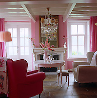 A jewel-like effect is created in the living room of this 18th century Dutch house by contrasting white gloss paint in the woodwork and fire surround with pink walls and fabrics