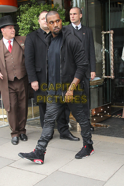 Kanye West.Leaving his hotel, London, England..March 18th, 2012.full length red black jacket top jeans denim sneakers trainers walking goatee facial hair .CAP/HIL.©John Hillcoat/Capital Pictures.