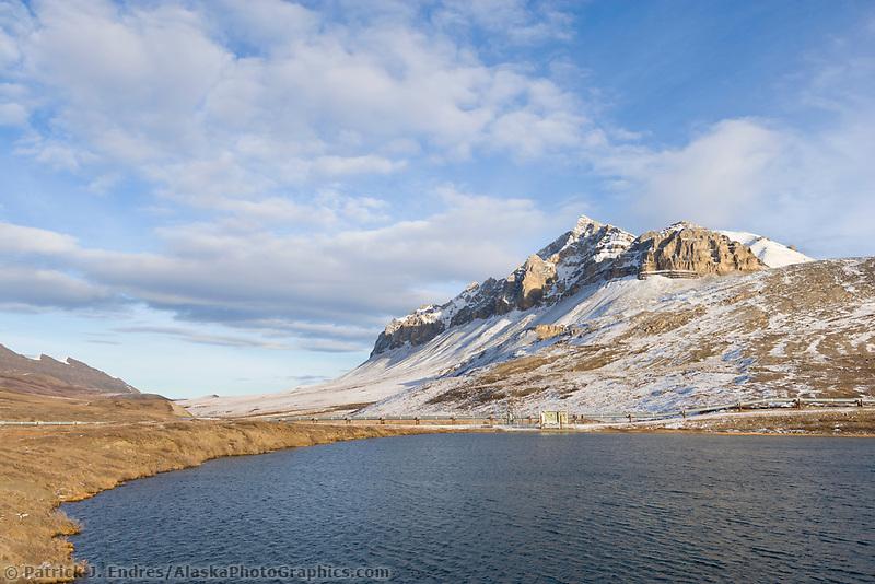 Trans Alaska oil pipeline crosses small tundra pond by Atigun river, Arctic, Alaska.