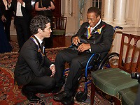 Thomas Kail, left, and wayne Shorter, right, two of the recipients of the 41st Annual Kennedy Center Honors, converse after posing for a group photo following a dinner hosted by United States Deputy Secretary of State John J. Sullivan in their honor at the US Department of State in Washington, D.C. on Saturday, December 1, 2018.  The 2018 honorees are: singer and actress Cher; composer and pianist Philip Glass; Country music entertainer Reba McEntire; and jazz saxophonist and composer Wayne Shorter. This year, the co-creators of Hamilton, writer and actor Lin-Manuel Miranda; director Thomas Kail; choreographer Andy Blankenbuehler; and music director Alex Lacamoire will receive a unique Kennedy Center Honors as trailblazing creators of a transformative work that defies category.<br /> CAP/MPI/RS<br /> &copy;RS/MPI/Capital Pictures