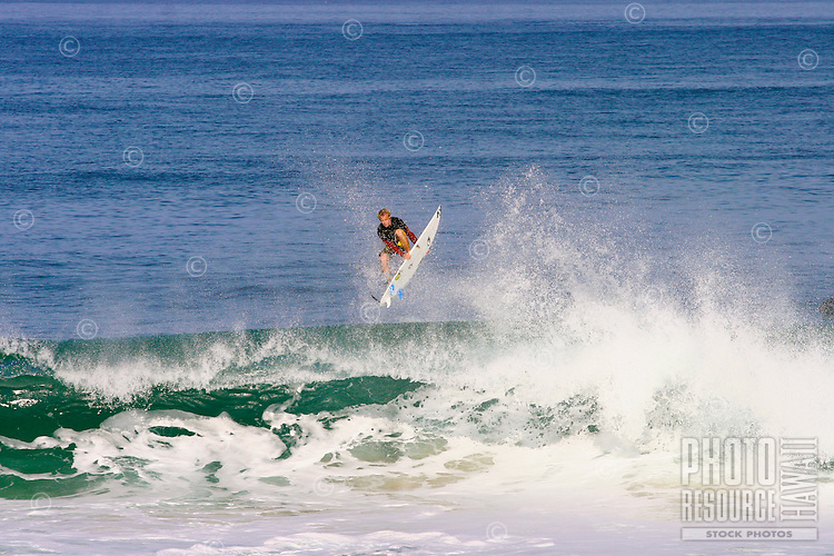 A surfer does an air off of the end section at Off the Wall on Oahu's North Shore. Off the Wall, also known as Kodak reef is a popular spot for both surfers and bodyboarders, as it is very easy to get great photoraphs.