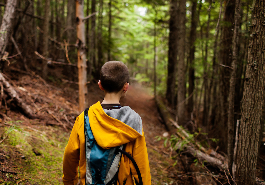 A young boy looks down a trail in North Idaho near Priest Lake in Bonner County.