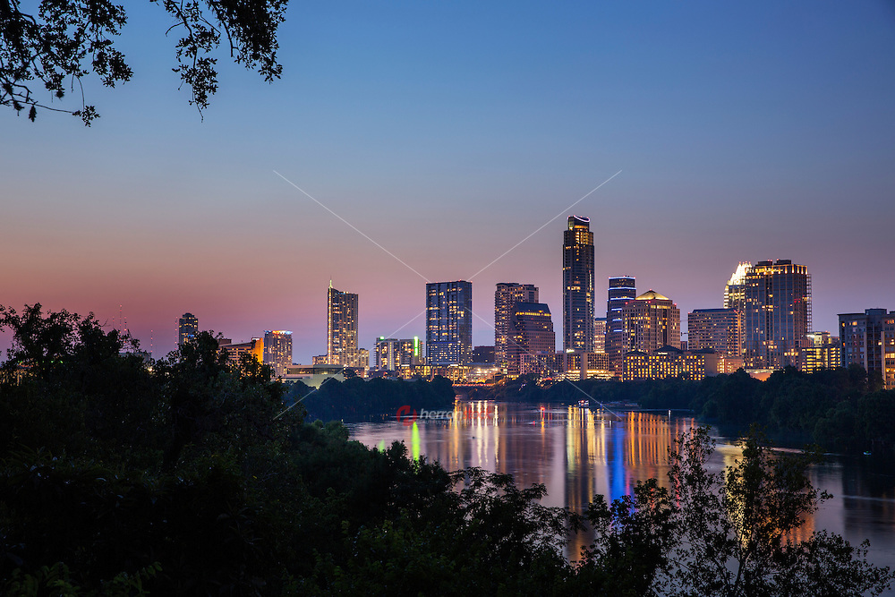 View of the majestic purple and pink violet crown sunset over the downtown Austin skyline and glass-like reflection of Lady Bird Lake as seen from the Travis Heights neighborhood.