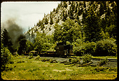Engine with 2 flat cars hauling pipe and caboose possibly in Monarch area.<br /> D&amp;RGW  Monarch area, CO