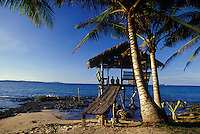 Couple in thatched hut on the ocean, Siargao Island, Philippines