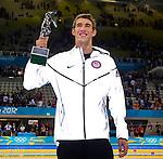 Engeland, London, 3 Augustus 2012.Olympische Spelen London.Michael Phelps toont zijn trofee voor de succesvolste olympiër ooit..Naast die 22 olympische medailles, ook een record, werd hij de eerste mannelijke zwemmer die een nummer bij drie Spelen op rij wist te winnen. Sterker, hij deed het twee keer, op de 100 vlinder en de 200 wissel. Zaterdagavond kreeg de Amerikaan in het Aquatics Centre een beeldje als beste olympiër ooit