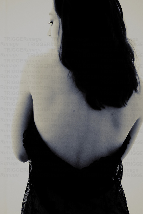 A young woman with black hair her back turned towards us wearing a black dress