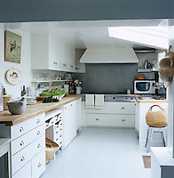 An impressive stainless steel cooking range is surrounded by painted pine cabinets in this contemporary country kitchen
