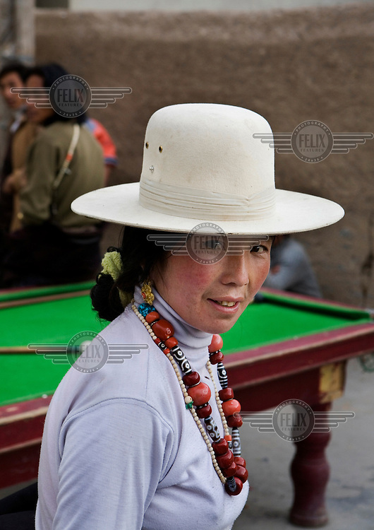A woman poses for a portrait next to a pool table.