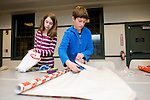SOUTHBURY, CT- 4 December 2014-120414EC07--   Charlie Bishop and Henry James of Southbury wrap gifts Thursday night to help out the Junior Friends of the Southbury Public Library. The team of young people had nearly 50 gifts wrapped within an hour. They also hosted a bake sale to raise money for the organization. Erin Covey Republican-American