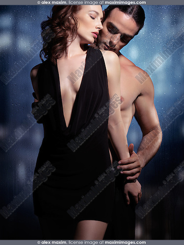 Sexy young couple artistic sensual portrait. Young woman in black dress and young man with bare torso standing at a wet window on a rainy night