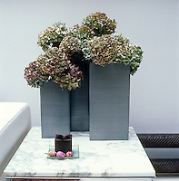 A simple arrangement of hydrangeas is displayed in an architectural zinc Christian Tortu vase on top of a marble side table