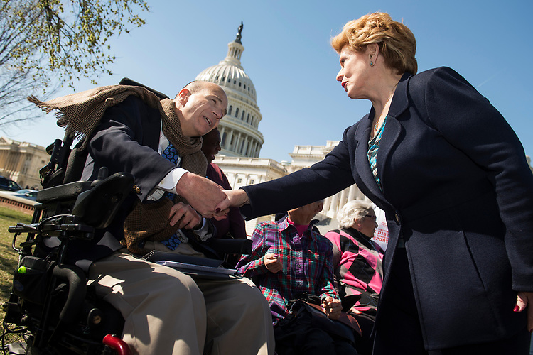 UNITED STATES - MARCH 9: Sen. Debbie Stabenow, D-Mich., greets Kent Keyser of the United Spinal Association, during a news conference in the Senate swamp to defend the Affordable Care Act, March 9, 2017. The event featured people who spoke about how the law helped deliver them medical coverage. (Photo By Tom Williams/CQ Roll Call)
