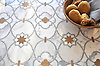 Vittoria, waterjet and hand-cut mosaic shown in Lagos Gold honed, Calacatta Tia and Allure polished is part of the Miraflores collection by Paul Schatz for New Ravenna.