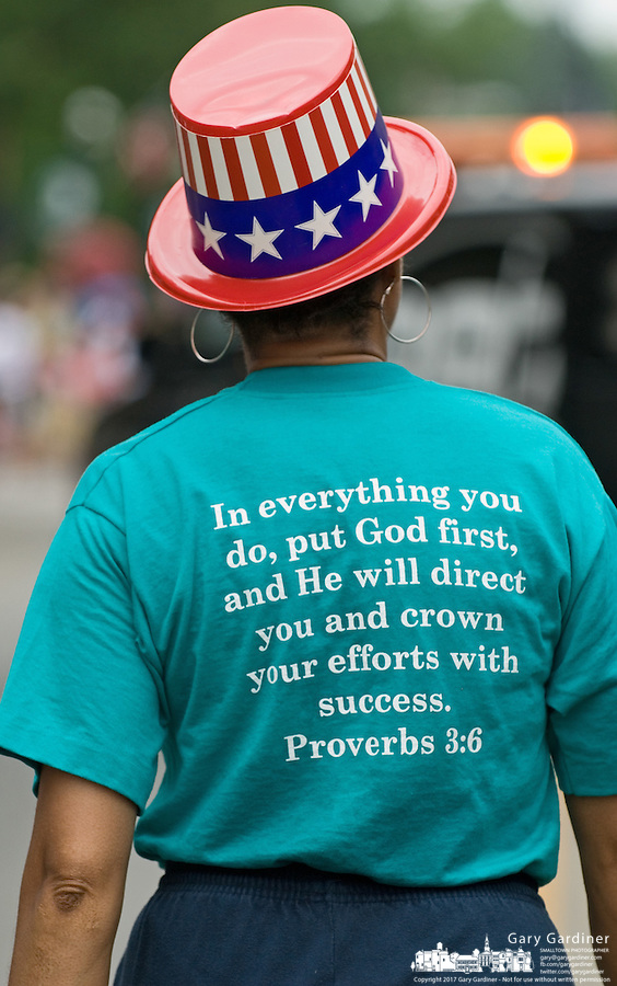 A woman walking beside a church float wears a patriotic colored hat and a t-shirt expressing her religious faith during the July 4, 2006, parade through Westerville, Ohio.<br />
