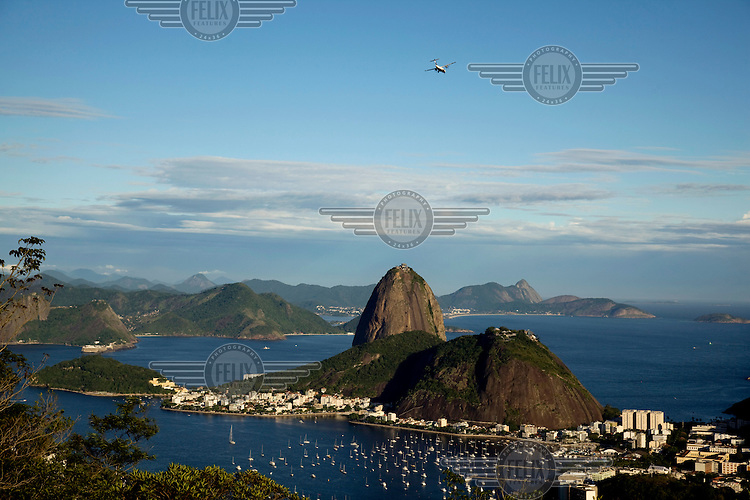 A light aircraft flies above the iconic Sugar Loaf Mountain as seen from the Santa Marta viewpoint.