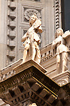 Details of two statues on the facade of the Duomo, Cathedral in Como, Italy.