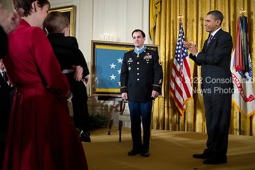 United States President Barack Obama applauds after awarding former Staff Sergeant Clinton Romesha the Medal of Honor for conspicuous gallantry during a ceremony in the East Room of the White House, February 11, 2013. At left, Romesha's wife Tammy holds their 2-year-old son, Colin. .Mandatory Credit: Pete Souza - White House via CNP