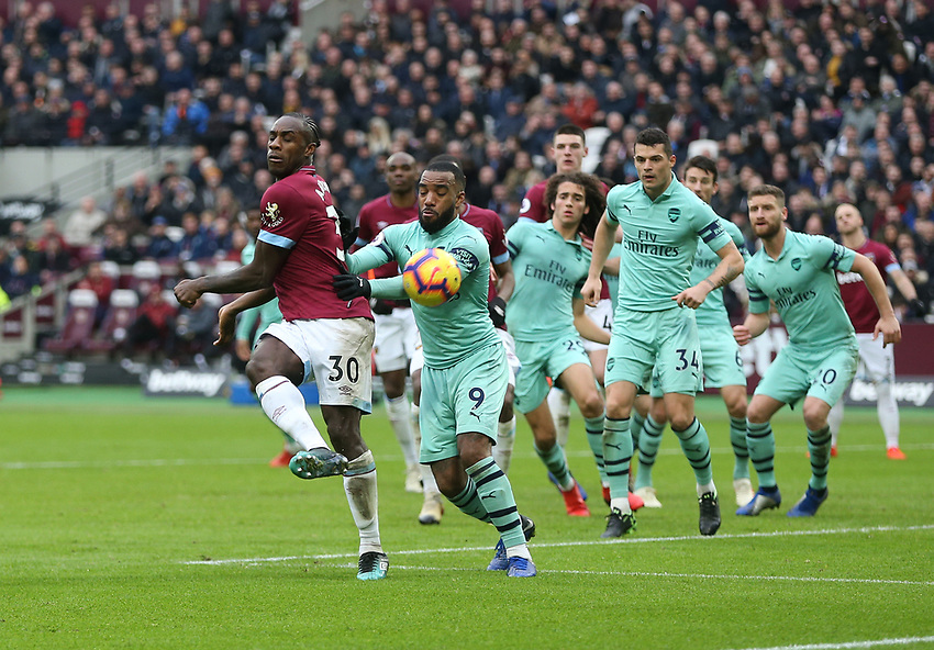 West Ham United's Michail Antonio flicks the ball on under pressure from Arsenal's Alexandre Lacazette<br /> <br /> Photographer Rob Newell/CameraSport<br /> <br /> The Premier League - West Ham United v Arsenal - Saturday 12th January 2019 - London Stadium - London<br /> <br /> World Copyright © 2019 CameraSport. All rights reserved. 43 Linden Ave. Countesthorpe. Leicester. England. LE8 5PG - Tel: +44 (0) 116 277 4147 - admin@camerasport.com - www.camerasport.com