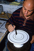 Ceramics, Nabeul, Tunisia.  Applying Design to Ceramic.  Using a Wheel to Trace Concentric Circles onto a Plate.  Le Caravane Workshop.