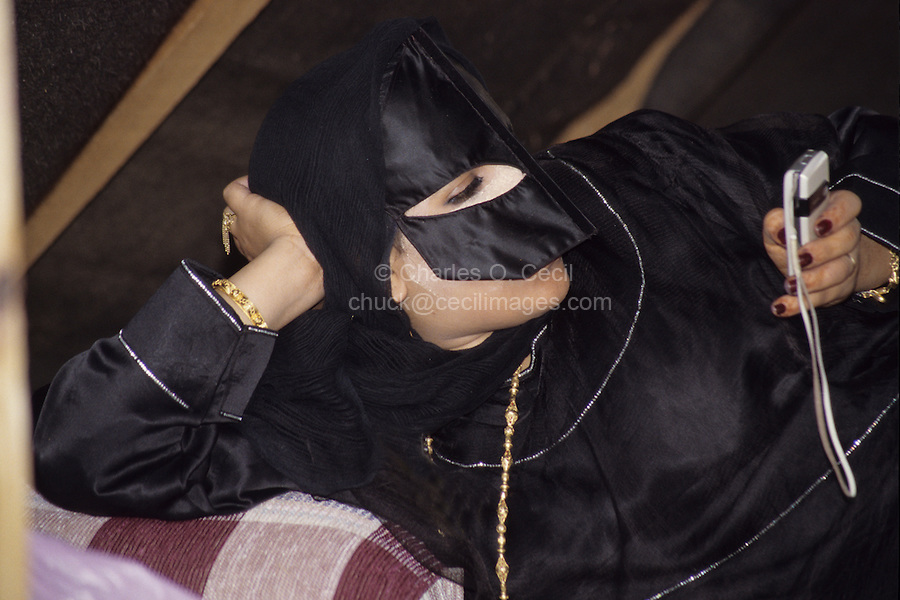 Masirah, Oman, Arabian Peninsula, Middle East - Masked Omani Woman from Masirah Using Cell Phone.  She is wearing a face mask known as a birqa.  The use of cell phones has revolutionized communications within Oman.  Cosmetic applied under her eye reduces the glare of the sun.