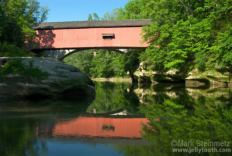 View looking upstream at the Narrows Covered Bridge, built in 1883 by Joseph A. Britton, over Sugar Creek in Parke County, Indiana, USA.