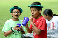 NWA Democrat-Gazette/DAVID GOTTSCHALK  Irvin Martinez (left), 10, and Alfredo Hernandez, 9, enjoy a frozen ice drink Friday, July 14, 2017, prepared by the Fayetteville Public Library at the 10th annual CDBG in the Park picnic at the Walker Park Pavilion in Fayetteville. The city's Community Development Block Grant held the picnic to share  information with  citizens about the programs that CDBG has to offer and to celebrate its investment in the community.  The event featured a free lunch, cold treats, family-friendly activities and information booths.