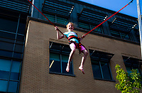 NWA Democrat-Gazette/CHARLIE KAIJO Ava Evans, 9, of Bentonville jumps on the Crazy Flipping bungee trampoline during the First Friday event, Friday, July 6, 2018 at the Downtown Square in Bentonville. <br />