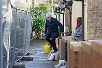 Pictured: Jeremy Corbyn jumps over a flood barrier defence of one of the houses affected by the floods. Thursday 20 February 2020<br /> Re: Jeremy Corbyn, the leader of the Labour Party visits the area of Rhydyfelin near Pontypridd, south Wales, UK.
