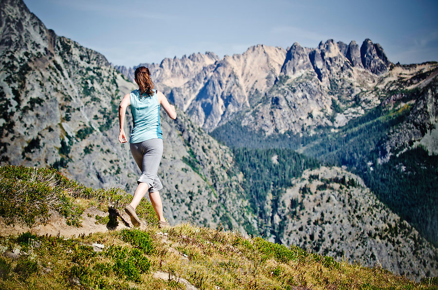 A young woman trail running through a spectacular alpine landscape in early Fall, Maple Pass, North Cascades National Park, WA.