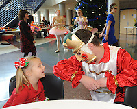 NWA Media/ANDY SHUPE - James Miskimen of Rogers, right, speaks with Reagan Oliver, 3, of Rogers during the Sugar Plum Tea Party Sunday, Dec. 7, 2014, at Rogers High School. Members of the Ballet Westside Performing Company in Rogers hosted the event and spent time with visitors prior to their second performance of The Nutcracker in the school's performing arts center.