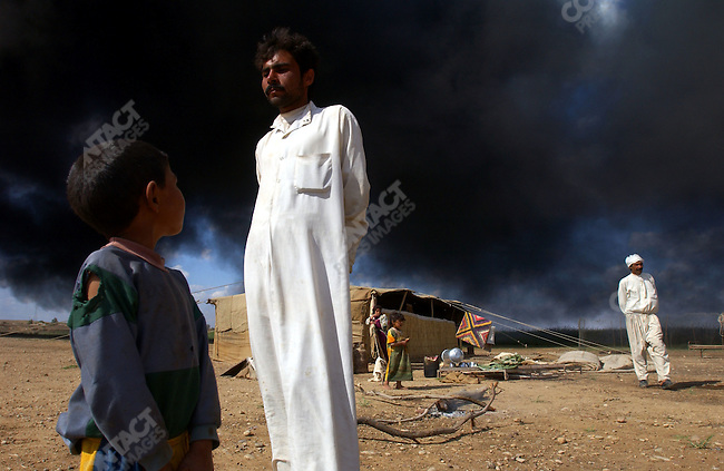 A family of Bedouinc stood near their tent and a burning pit of oil made originally as a defence for the town of Samarra, near Tikrit, but mysteriously set alight in the last few days. April 28, 2003