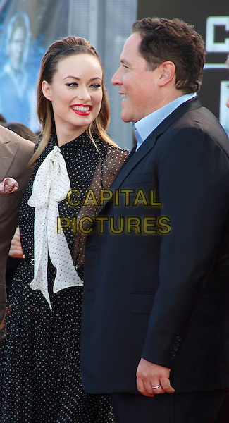 OLIVIA WILDE & JON FAVREAU.UK Premiere of 'Cowboys and Aliens' at the Cineworld cinema at the O2 Arena, London, England..August 11th 2011.half length black white pussybow sheer polka dot dress side panel hairband red lipstick suit profile .CAP/ROS.©Steve Ross/Capital Pictures