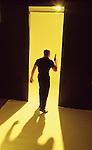 Man with gun on yellow seamless walking away from camera