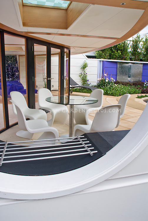 Covered patio porch, modern upscale. Design: Dean Herald<br /> outdoor fireplace grill, outdoor room, table and chairs, house, privacy wall, stone patio, futuristic style, flowers, climbing vines, trees, white and purple and cream