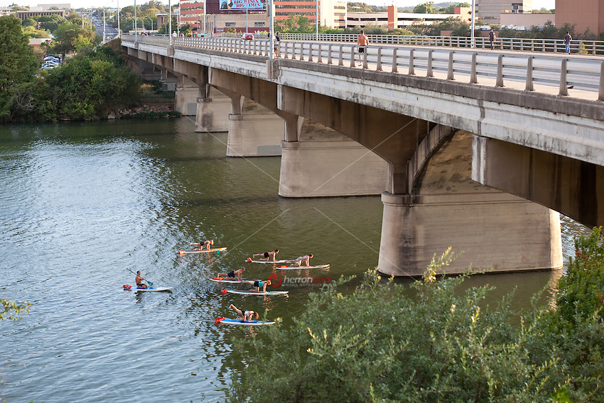 The Stand Up Paddling Fitness Craze is popular exercise activity on Lady Bird Lake in Austin, Texas