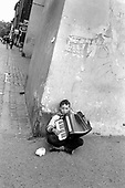A boy plays the accordion for small change on a Krakow street.
