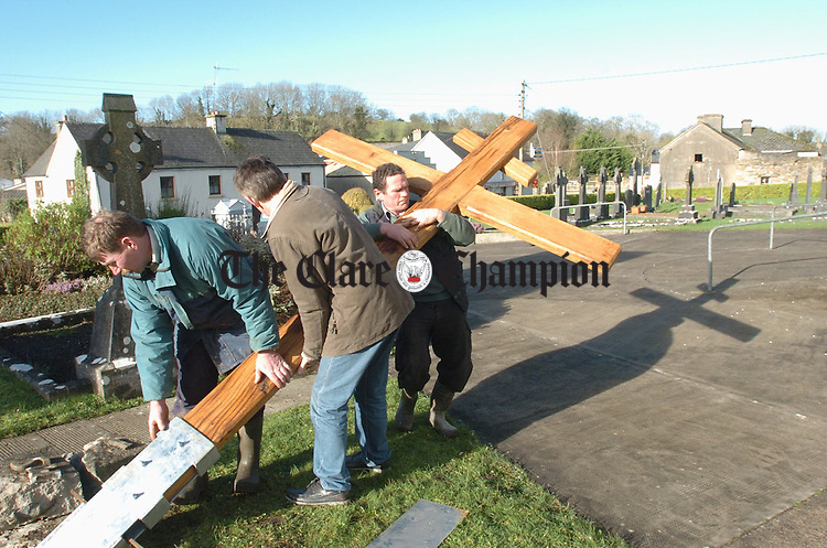 Vincent Dinan, craftsman Con Mc Guinness and woodworker Pat Minogue erecting a cross, made from wood recycled from the Jeanie Johnston project, at Bodyke church. the original cross was erected as a famine memorial in 1895. Photograph by John Kelly.