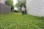 Mikhail Mazo, 52, a Russian immigrant, walks beside his home with the warning notice he received for not trimming his lawn from the suburban Chicago municipality of Buffalo Grove, Illinois on July 2, 2009.