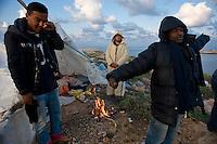 Immigrati Tunisini appena svegliati dopo aver passato la notte in una tenda costruita con le poche cose a disposizione dopo essere sbarcati a Lampedusa.