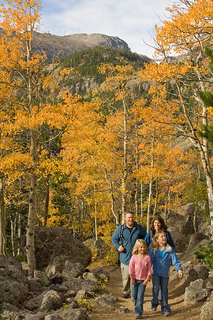 Family hiking on trail through the golden colors of autumn in aspen stands above Bear Lake on a September morning in Rocky Mountain National Park, Colorado