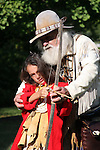 Mountain Man father figure showing young Native American Indian boy how to shoot bow and arrow
