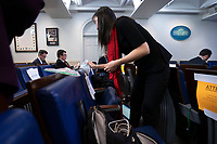 A member of media wipes down their seat prior to a news conference with United States President Donald J. Trump in the Brady Press Briefing Room of the White House in Washington, DC on Saturday, March 21, 2020.  Credit: Stefani Reynolds / Pool via CNP/AdMedia