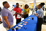 St. Louis Metropolitan Police Sgt. Christy Allen (right) speaks to (from left) Arlando Van Hook of Florissant, and Laterell Moore and Kelly Haywood, both from Collinsville, at a Diversity Fair sponsored by the St. Louis County branch of the Ethical Society of Police. Haywood and Moore are dating and both want to become police officers. The fair was held at Hazelwood Central High School on Saturday August 11, 2018 with police agencies from ten different jurisdictions represented.   Photo by Tim Vizer