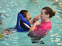 STAFF PHOTO BEN GOFF  @NWABenGoff -- 12/05/14 Sarah Smith, a swimming instructor at the Walton Life Fitness Center, helps Hayden Cothran, 8, learn to swim during Welcome to Swim Night, an event coordinated by the Bentonville School District special education department and Bike Bentonville to introduce kids with special needs to swimming, at the Walton Life Fitness Center in Bentonville on Friday Dec. 5, 2014. A similar event in October introduced special needs students in the district to bicycling, and future events will expose them to such activities as golf, rock climbing and fishing.