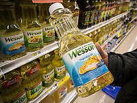 A shopper chooses a bottle of Wesson vegetable oil in a supermarket in New York on Tuesday, May 30, 2017. Conagra Brands is reported to be selling its Wesson oil brand to J.M. Smucker Co. for approximately $285 million. Wesson will join Smucker's Crisco oil brand. (© Richard B. Levine)