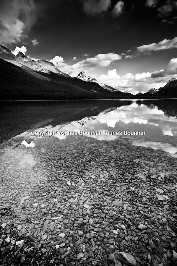 Moving clouds over waterfowl lake reflection in the late afternoon light black and white