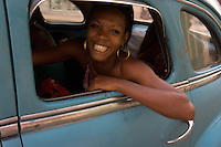 black girl with golden ear clips in blue oldtimer, Havana, Cuba